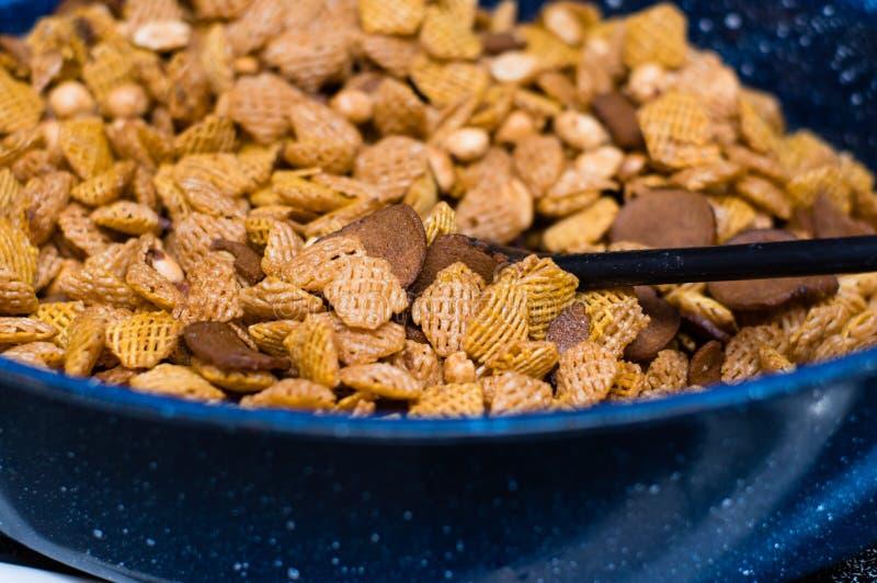 La mezcla del partido del cereal con los cacahuetes revolvió adentro una cacerola azul foto de archivo libre de regalías