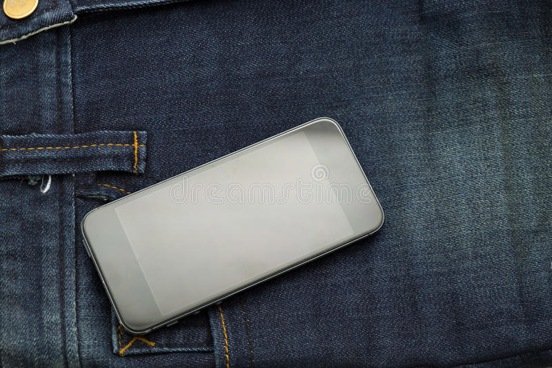 La mezclilla azul bastante vieja tiene la raya y teléfono elegante fotografía de archivo libre de regalías