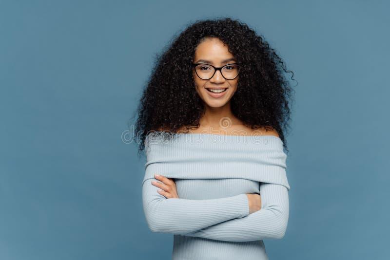 La mezza lunghezza sparata di giovane femmina felice ha espressione facciale sicura, tiene le armi piegate, vestito in maglione a fotografia stock