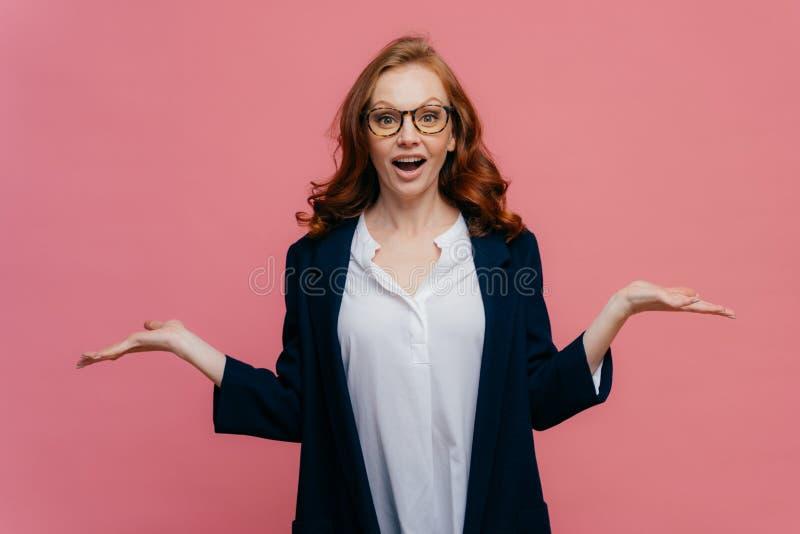 La mezza lunghezza sparata di signora confusa di affari alza le palme, fa vestirsi l'espressione facciale titubante, in vestito c immagine stock