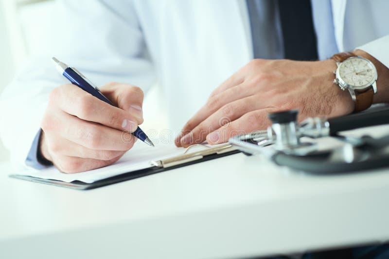 La mi section de l'inscription masculine de docteur ?crivent la prescription au patient ? la table de travail Panac?e et ?conomie image stock