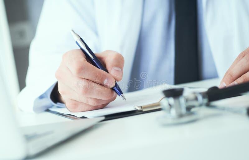 La mi section de l'inscription masculine de docteur ?crivent la prescription au patient ? la table de travail Panac?e et ?conomie images libres de droits