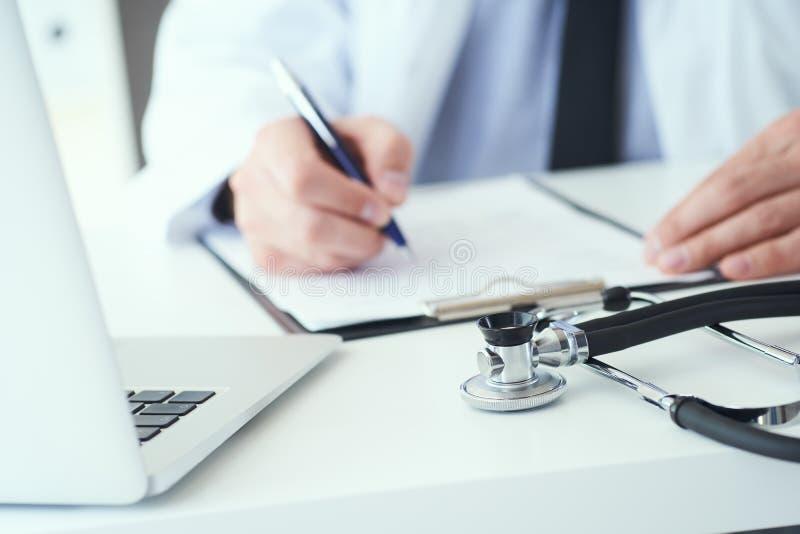 La mi section de l'inscription masculine de docteur ?crivent la prescription au patient ? la table de travail Panac?e et ?conomie image libre de droits