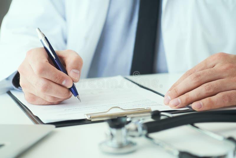 La mi section de l'inscription masculine de docteur ?crivent la prescription au patient ? la table de travail Panac?e et ?conomie photographie stock libre de droits