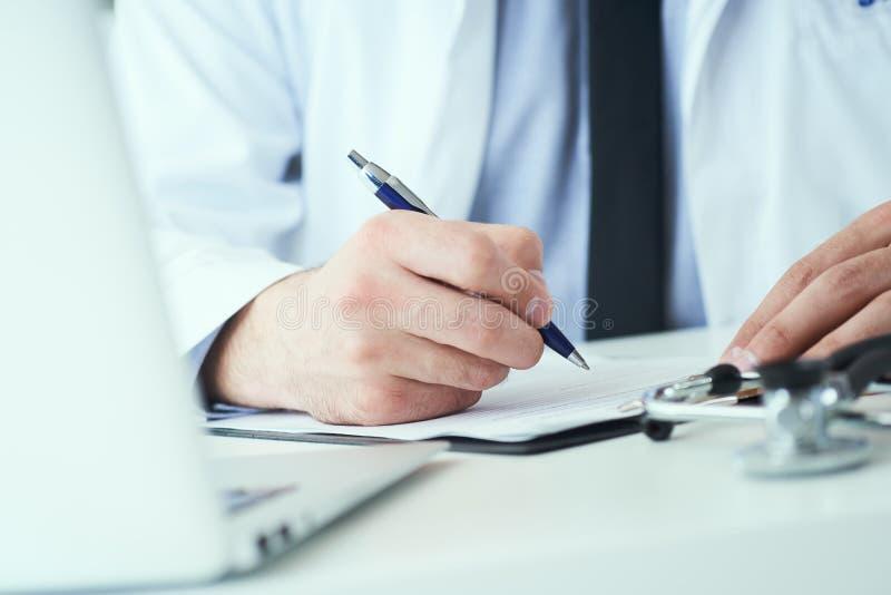 La mi section de l'inscription masculine de docteur ?crivent la prescription au patient ? la table de travail Panac?e et ?conomie photos stock