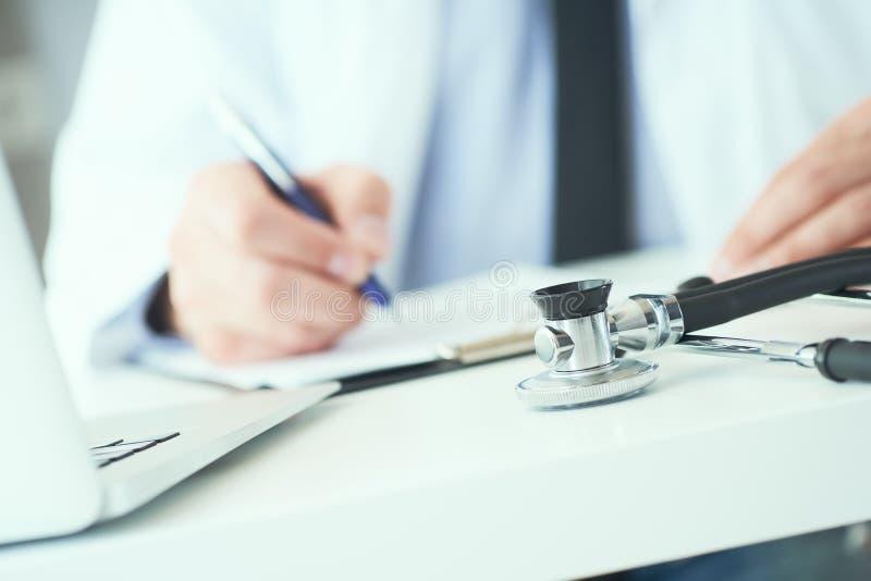La mi section de l'inscription masculine de docteur ?crivent la prescription au patient ? la table de travail Panac?e et ?conomie photographie stock
