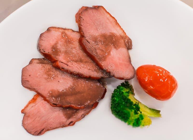 La miel asada cortó el cerdo en la placa blanca, comida tradicional china en el restaurante de lujo, visión superior foto de archivo libre de regalías