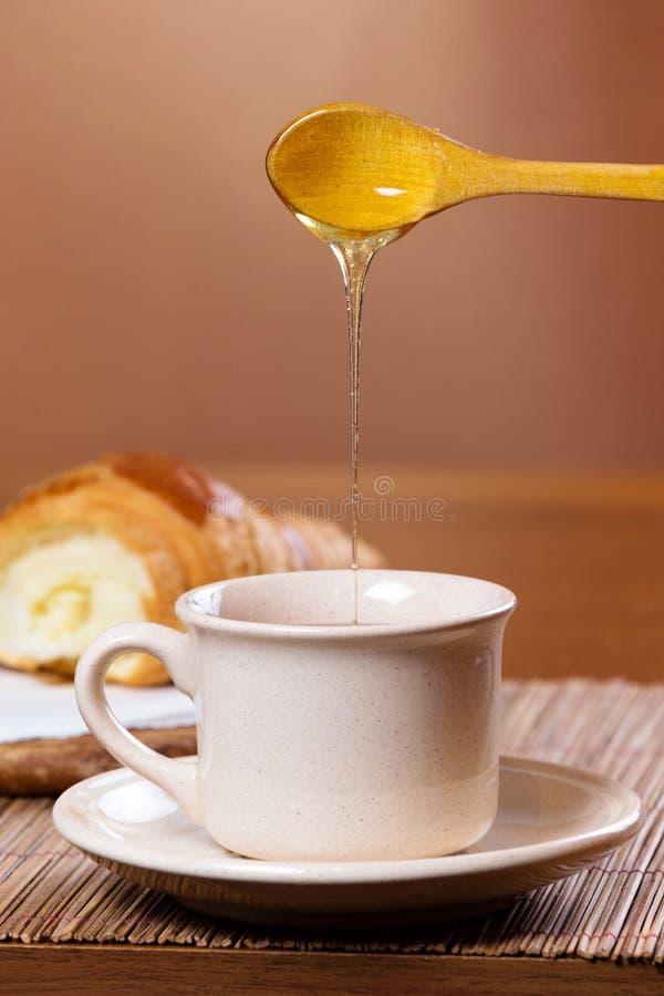 La miel de colada en té asalta imagenes de archivo