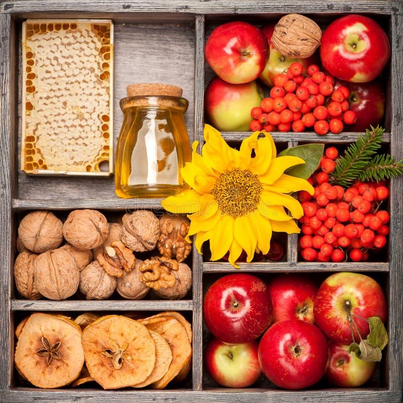 La miel, manzanas rojas, nueces, flores, girasoles, secó manzanas fotos de archivo