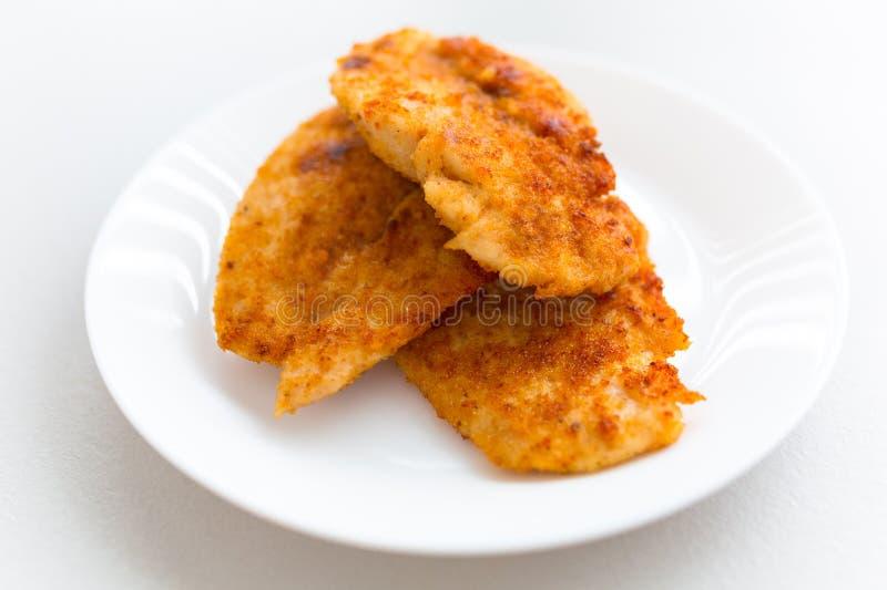 La miga de pan cubrió la pechuga de pollo frita en una placa blanca fotografía de archivo libre de regalías