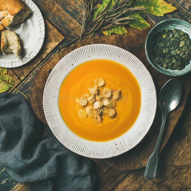 La minestra crema di riscaldamento della zucca con i crostini ed i semi, quadra il raccolto fotografia stock