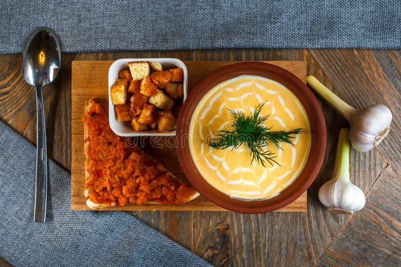 La minestra del formaggio ha schiacciato in un piatto dell'argilla è su un vassoio Accanto lui è un pezzo di pane, di cucchiaio e fotografie stock