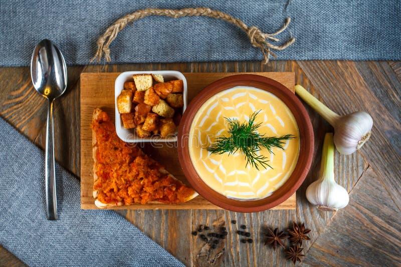 La minestra del formaggio ha schiacciato in un piatto dell'argilla è su un vassoio Accanto lui è un pezzo di pane, di cucchiaio e immagine stock libera da diritti