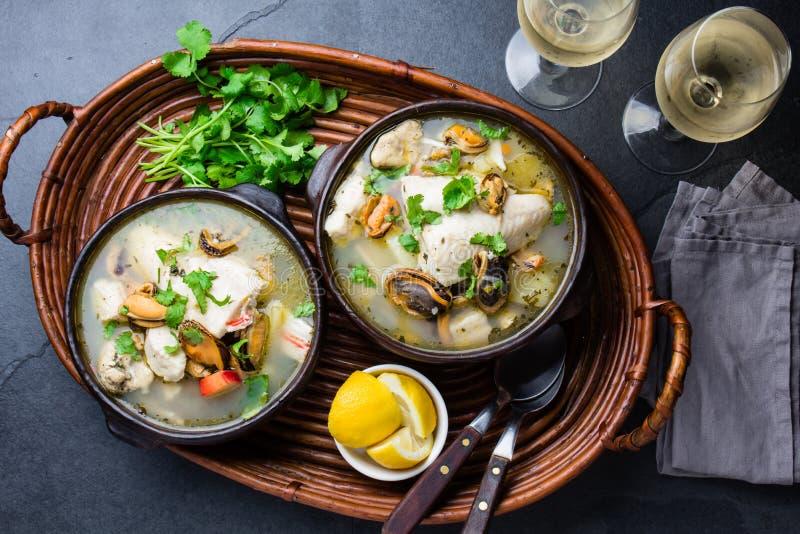 La minestra del pesce dei frutti di mare in ciotole dell'argilla è servito con vino bianco freddo Vista superiore, spazio della c fotografia stock