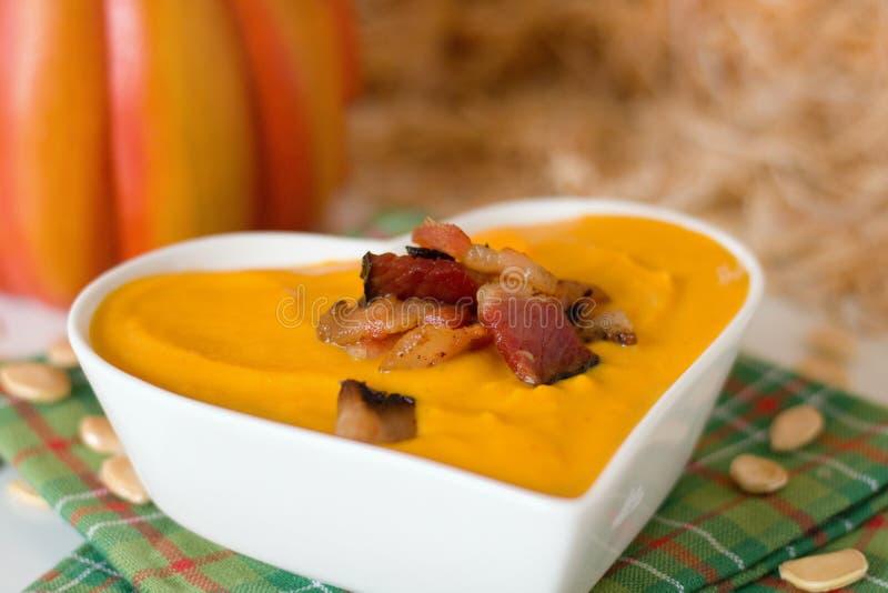La minestra della zucca con bacon nel cuore ha modellato la ciotola immagine stock libera da diritti