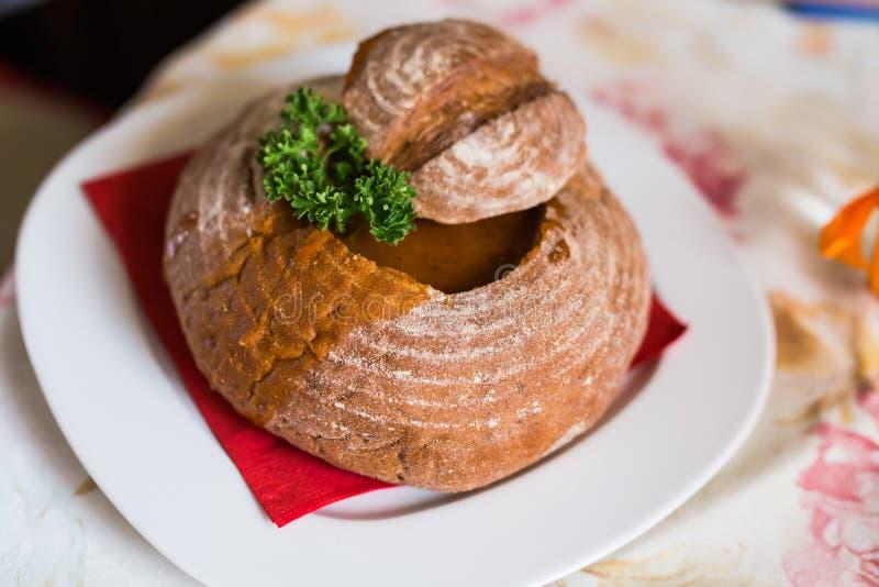 La minestra di goulash con il manzo, salsiccia della carne e della patata, è servito in una ciotola del pane immagine stock