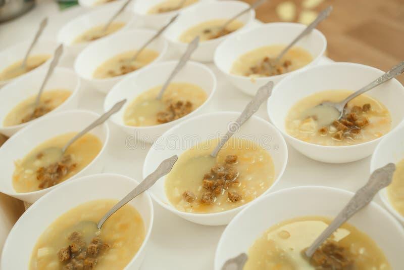 La minestra di verdura rassodata del pranzo, i cracker, i piatti, cucchiaio è stata preparata per i bambini sulla tavola lunga ne immagini stock