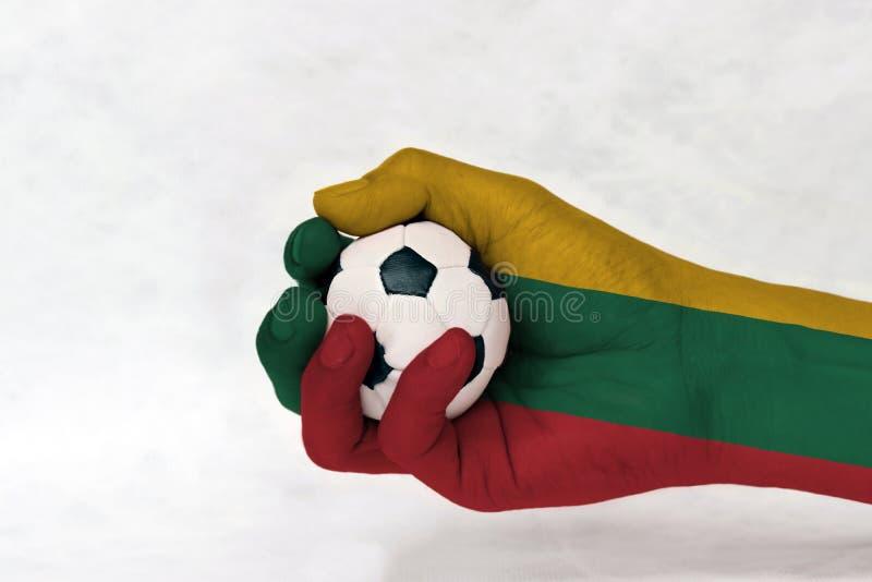 La mini bola del fútbol en la bandera de Lituania pintó la mano en el fondo blanco imagen de archivo libre de regalías