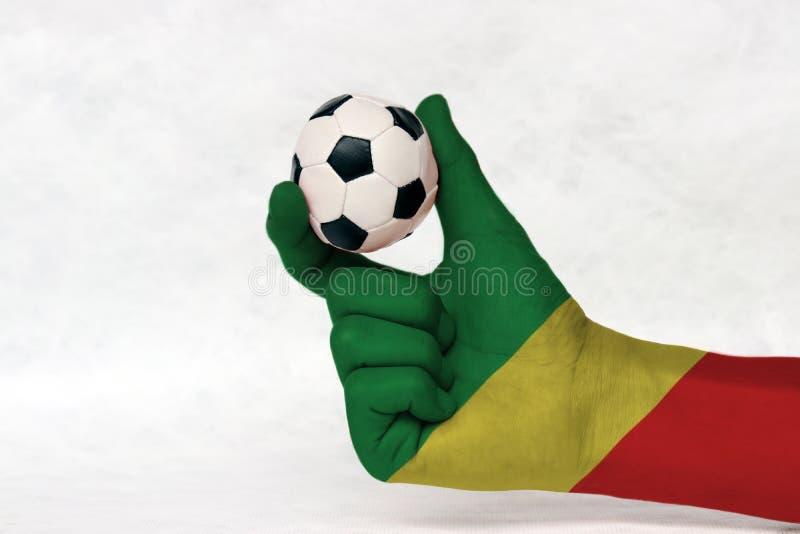 La mini bola del fútbol en la mano pintada bandera de Congo, la lleva a cabo con el finger dos en el fondo blanco imagen de archivo libre de regalías
