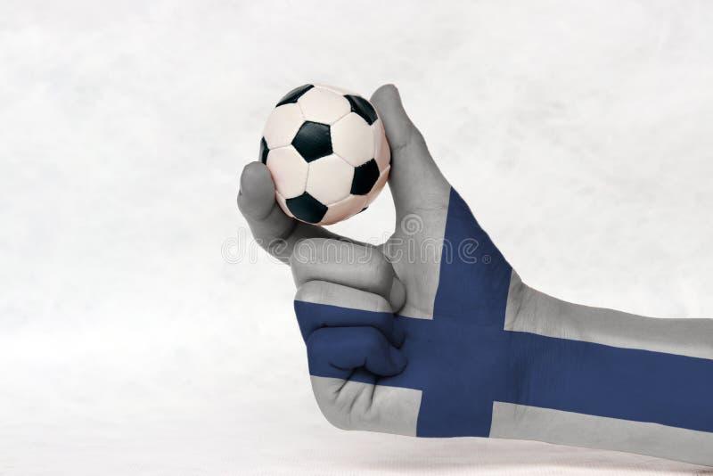 La mini bola del fútbol en la mano pintada bandera de Finlandia, la lleva a cabo con el finger dos en el fondo blanco fotografía de archivo libre de regalías