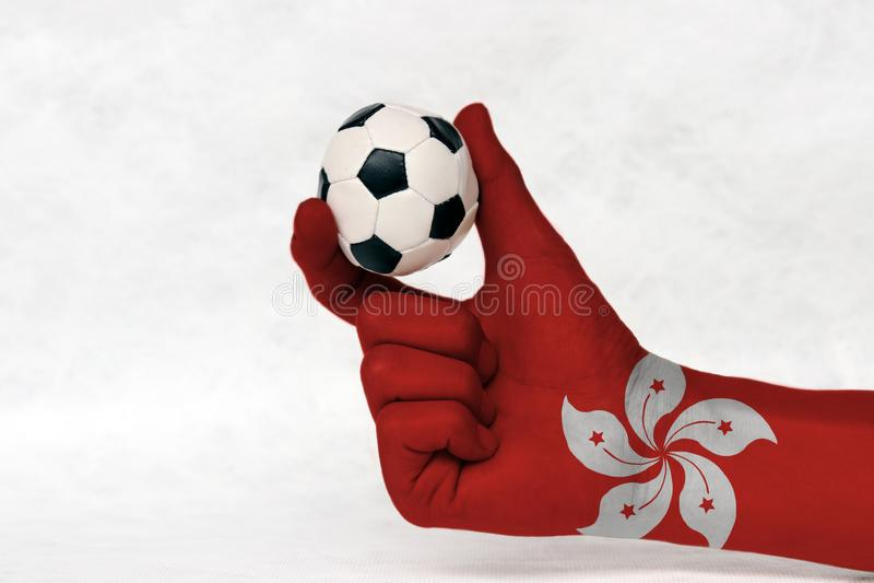 La mini bola del fútbol en la mano pintada bandera de Hong-Kong, la lleva a cabo con el finger dos en el fondo blanco foto de archivo