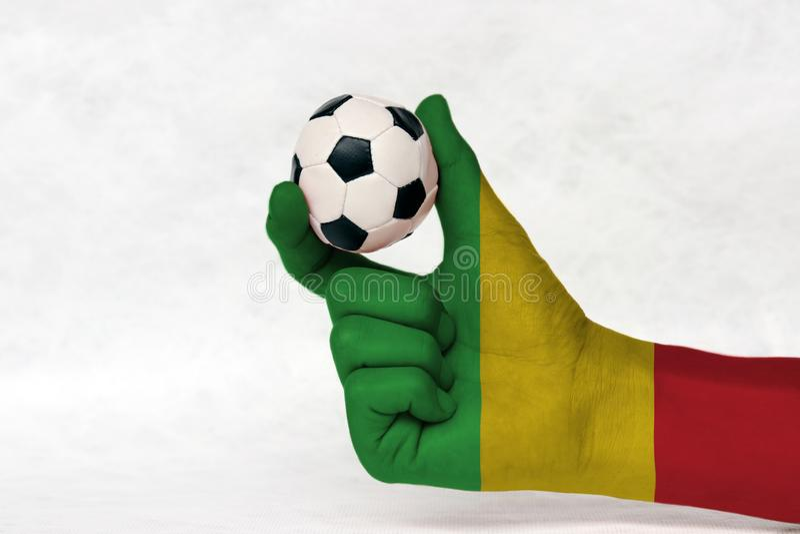La mini bola del fútbol en la mano pintada bandera de Malí, la lleva a cabo con el finger dos en el fondo blanco tricolor del oro foto de archivo libre de regalías