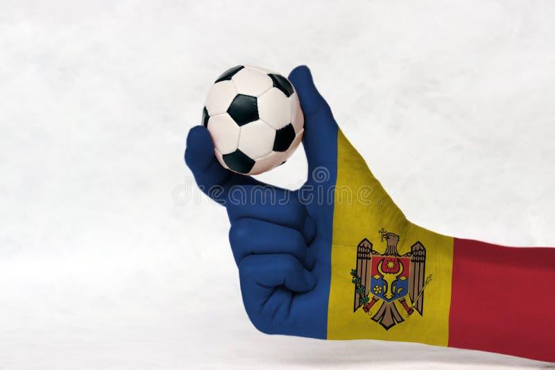 La mini bola del fútbol en la mano pintada bandera del Moldavia, la lleva a cabo con el finger dos en el fondo blanco fotos de archivo