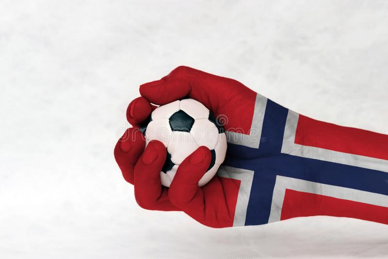La mini boule du football dans le drapeau de la Norvège a peint la main sur le fond blanc Concept de sport ou le jeu dans la poig images stock