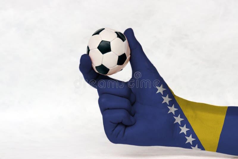 La mini boule du football dans la main peinte par drapeau de la Bosnie-Herzégovine, la tiennent avec le doigt deux sur le fond bl photos libres de droits