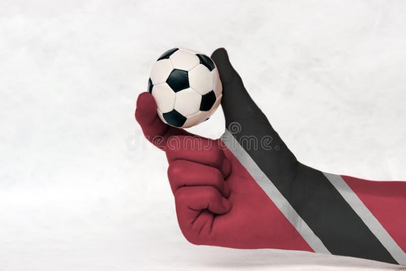 La mini boule du football dans la main peinte par drapeau du Trinidad-et-Tobago, la tiennent avec le doigt deux sur le fond blanc photographie stock libre de droits