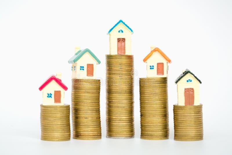 La mini maison sur la pile de pièces de monnaie d'isolement sur le fond blanc, investissement immobilier, épargnent l'argent avec images stock