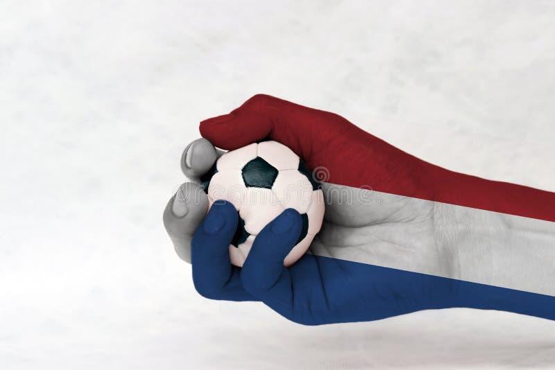 La mini palla di calcio in bandiera olandese ha dipinto la mano su fondo bianco Concetto dello sport o il gioco in maniglia o nel fotografia stock