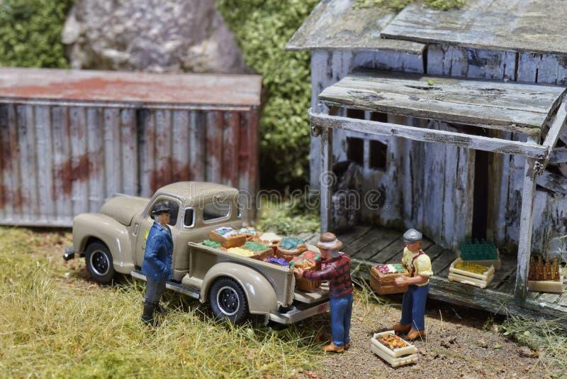 La miniatura del granjero que mira a los trabajadores que llevan mercancías del producto al carcoge en fábrica del almacén de d foto de archivo