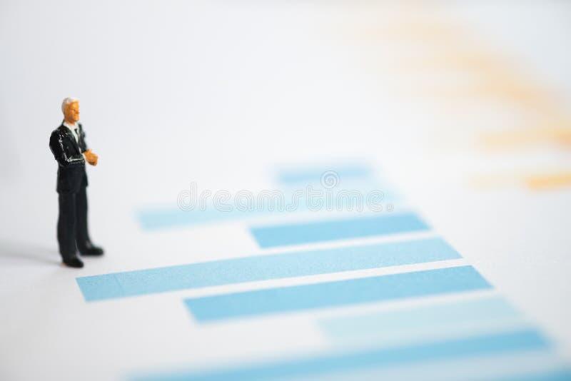La miniatura figura a los hombres de negocios que se colocan en una carta del gráfico financiera imágenes de archivo libres de regalías