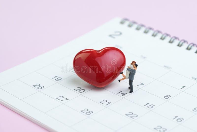 La miniature figure les couples doux se tenant avec le sha rouge brillant de coeur photographie stock