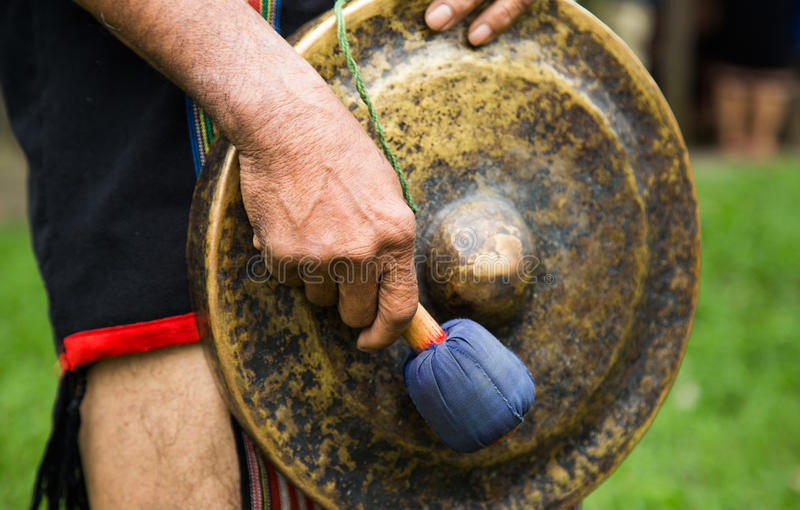 La minorité équipent dans la robe traditionnelle frappant un gong de cuivre photo stock