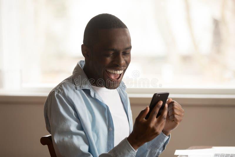 La mirada africana del individuo en las grandes noticias leídas teléfono móvil siente feliz foto de archivo libre de regalías
