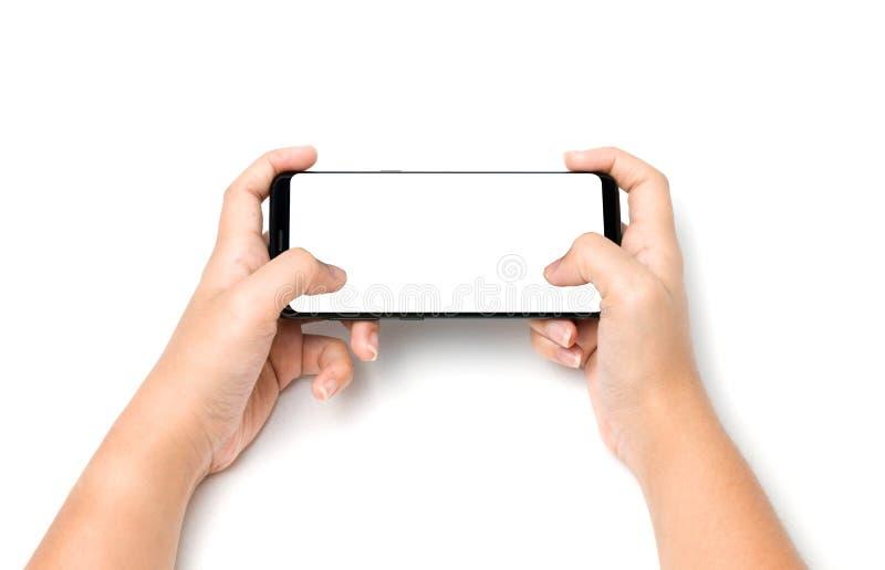 La mirada del teléfono celular de tenencia de la mano le gusta jugar a un juego imagenes de archivo