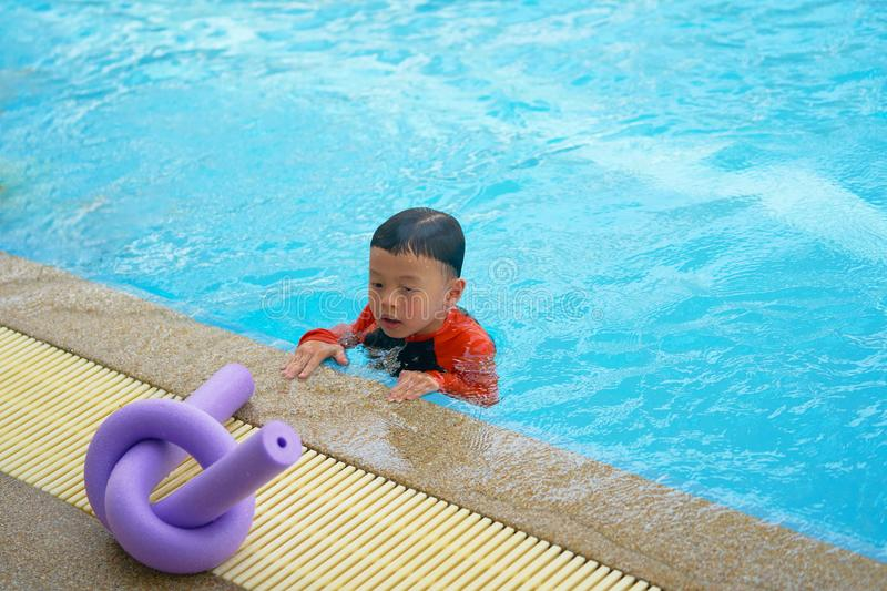 La mirada fija del muchacho en la espuma de los tallarines para aprende la natación en el lado del poo del agua fotos de archivo