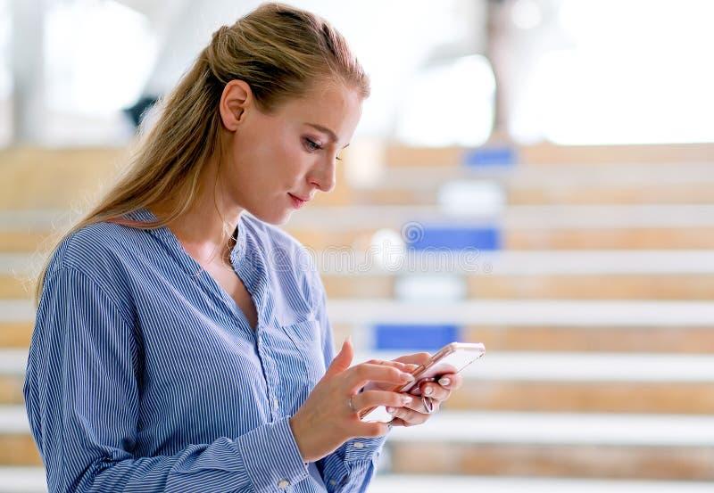 La mirada hermosa blanca caucásica de la mujer de negocios en su teléfono móvil y el soporte en la manera del paseo del tren de c imagen de archivo libre de regalías