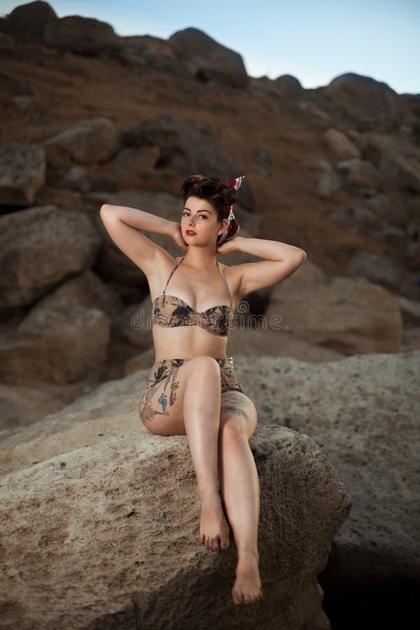 La mirada modela vistió a la muchacha que se sentaba en las rocas foto de archivo libre de regalías
