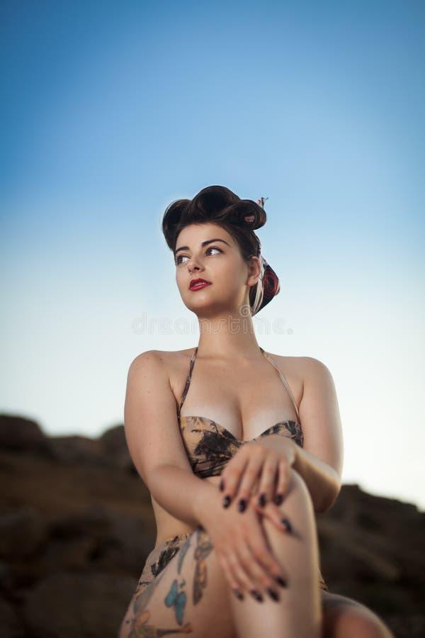 La mirada modela vistió a la muchacha que se sentaba en las rocas imágenes de archivo libres de regalías