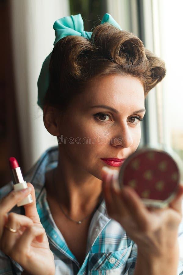 La mirada modela vistió las pinturas de la mujer sus labios con el lápiz labial rojo fotos de archivo libres de regalías