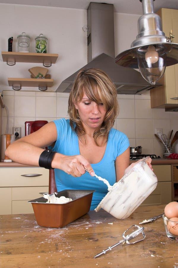 La mise de la pâte de gâteau dans elle est forme image stock