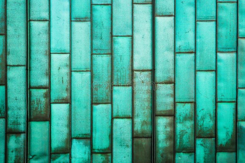 La mise en gaine vert cuivre du bâtiment Le vieux métal grunge couvre de tuiles le mur Fond rustique balayé de texture de feuille images stock