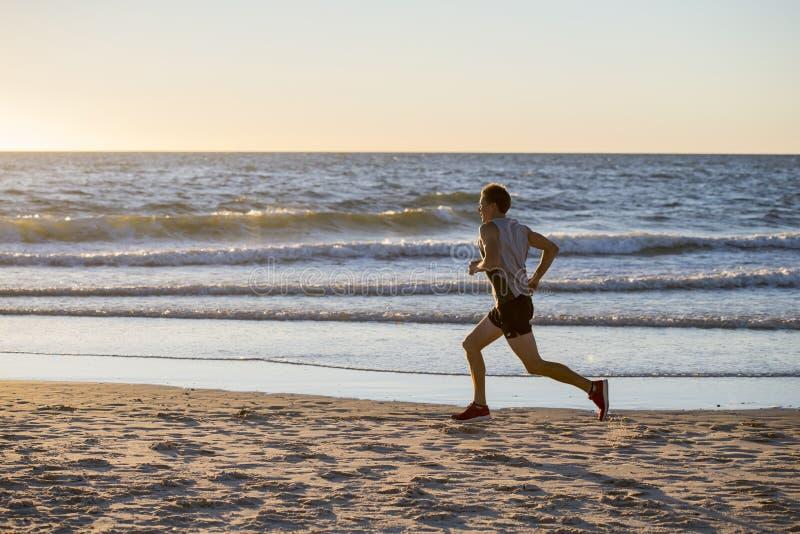 La misura atletica ed il forte corridore equipaggiano l'addestramento sulla spiaggia del tramonto dell'estate nel funzionamento d immagini stock