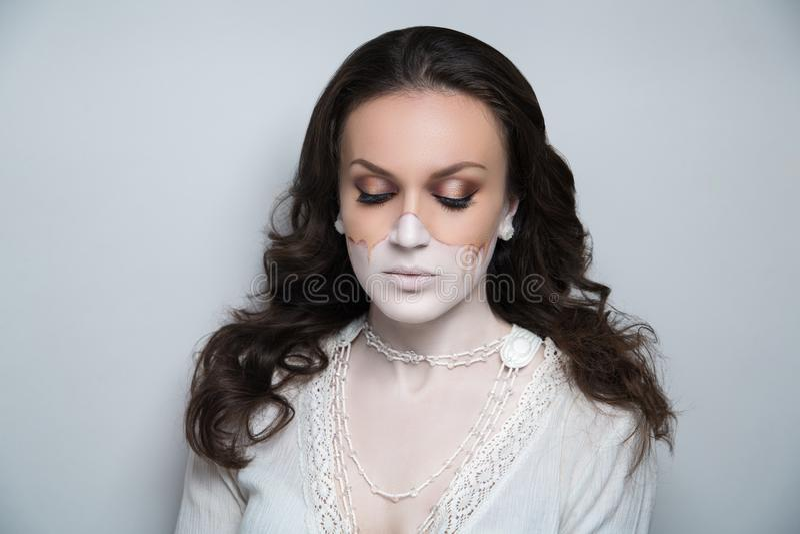 La mitad de la cara femenina se sombrea con la mujer beige de la fundación compone fotos de archivo libres de regalías