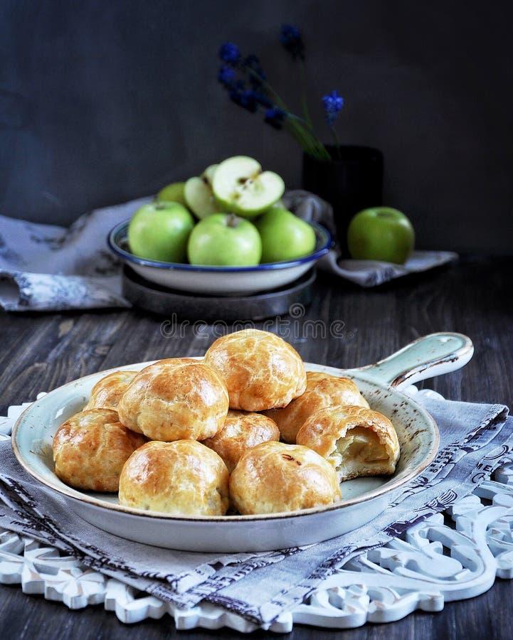 La mitad de manzanas coció en la pasta, bollos con las manzanas imágenes de archivo libres de regalías