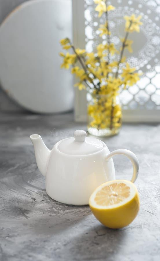 La mitad del limón fresco y la tetera blanca están en fondo gris foto de archivo