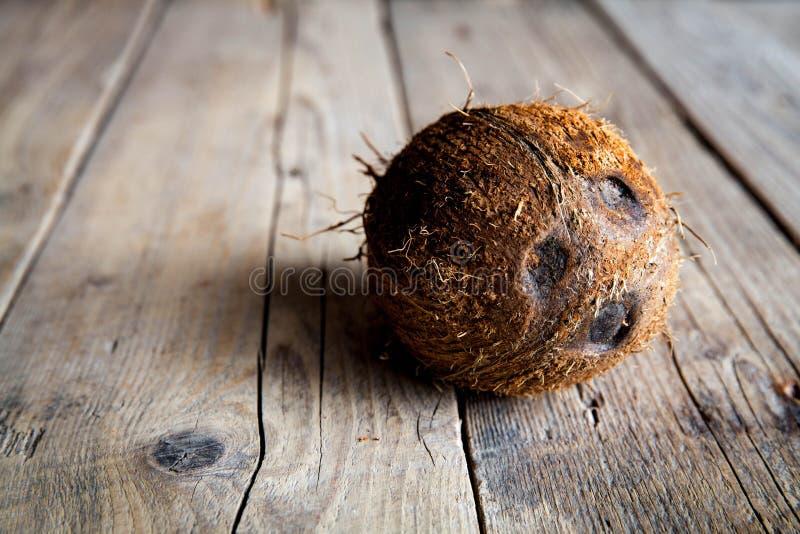 La mitad madura cortó el coco en un fondo de madera La mitad madura cortó el coco en un fondo de madera Crema y aceite del coco fotografía de archivo libre de regalías